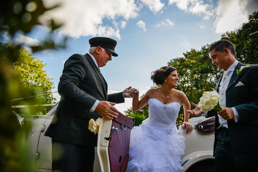 bride getting out of the car for the wedding reception at Weston Hall Hotel in Bulkington