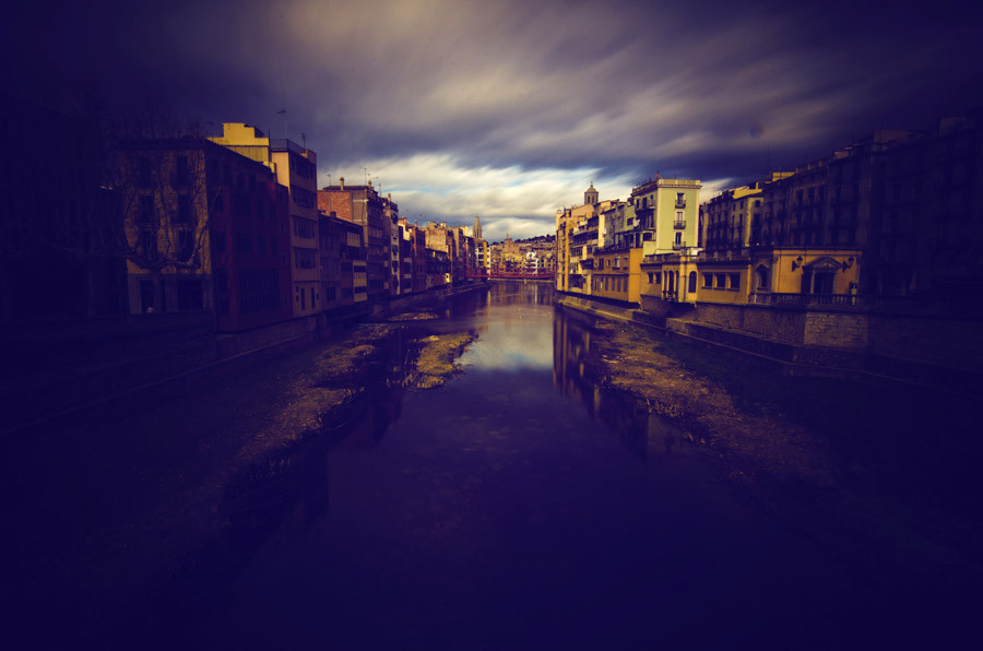 Girona river and church with dark sky. Captured by Richard Hadley, wedding and portrait photographer.